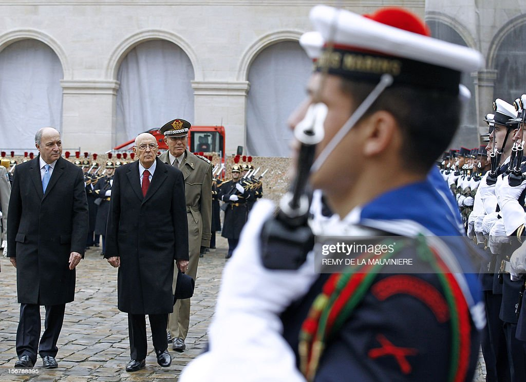 French foreign minister Laurent Fabius (L) and Italian President Giorgio Napolitano, review troops during a ceremony at the Invalides in Paris, on November 21, 2012. Giorgio Napolitano is on a two-day state visit in France. AFP PHOTO POOL Remy de la Mauviniere
