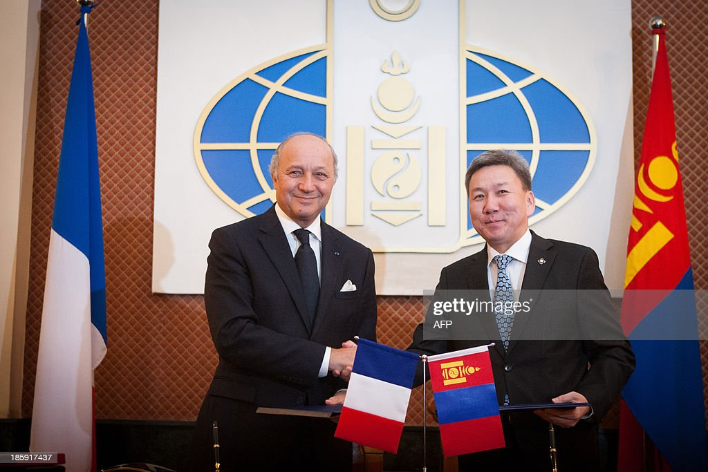 French foreign minister Laurent Fabius (L) shakes hands with Mongolian foreign minister Luvsanvandan Bold after signing a contract during his visit to Mongolia in Ulan Bator on October 26, 2013. French nuclear energy giant Areva signed a deal with Mongolia's state-owned Mon-Atom on Saturday to develop two uranium mines in the Gobi desert, officials said.