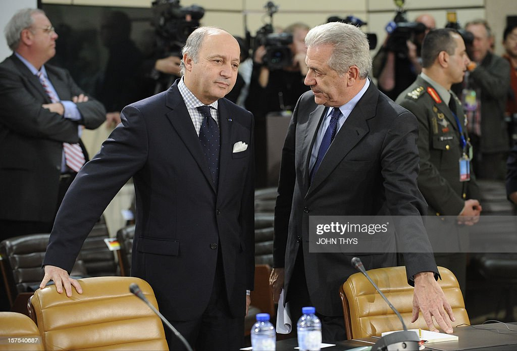 French Foreign Minister Laurent Fabius (L) speaks with his Greek counterpart Dimitrios Avramopoulos on December 4, 2012 at North Atlantic Treaty Organization (NATO) headquarters in Brussels during a meeting of foreign ministers from the 28 NATO member-countries to discuss Syria and Turkey's request for Patriot missiles to be deployed protectively on the Turkish-Syrian border. AFP PHOTO / JOHN THYS