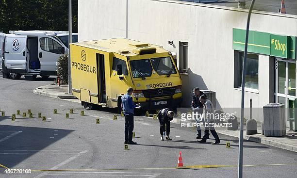 French forensic experts search for evidence near an armoured truck of the Prosegur company after it was attacked by a commando on October 6 2014 at a...