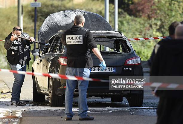 French forensic experts work on a burned car used by a commando during an attempted attack against an armored truck of the Prosegur company on...
