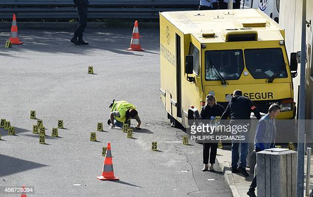 French forensic experts work on Prosegur's armoured truck attacked this morning by a commando on October 6 2014 in a gas station on the A47 motorway...