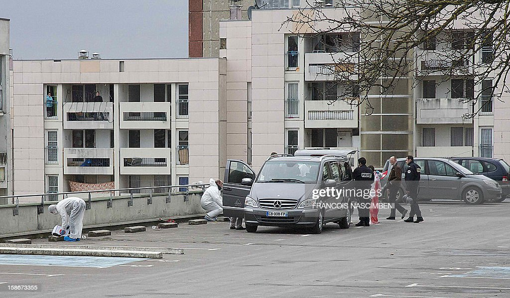 French forensic police investigators load into a funerary vehicle the body of a 17 year-old young man who was shot dead in the morning, on December 23, 2012 in the inner city area of ??Bernon in Epernay, northern France.