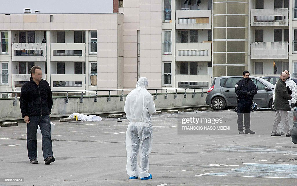 French forensic police investigators look for evidence near the body (L) of a 17 year-old young man who was shot dead in the morning, on December 23, 2012 in the inner city area of ??Bernon in Epernay, northern France.