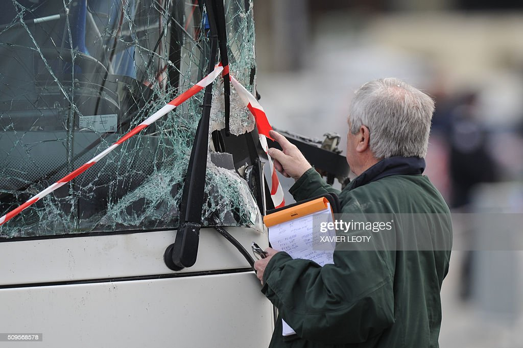 A French forensic police officer shows the point of impact of the accident, on the wreckage of a school minibus after it crashed into a truck in Rochefort on February 11, 2016, killing at least six children, police said, a day after another road accident involving a school bus left two youngsters dead. The head-on smash with a lorry carrying rubble came around 7:15 am (0615 GMT) in Rochefort in the western Charente-Maritime region. The school bus was carrying about 17 people, and three children suffered minor injuries in the accident, a police source said. / AFP / XAVIER LEOTY