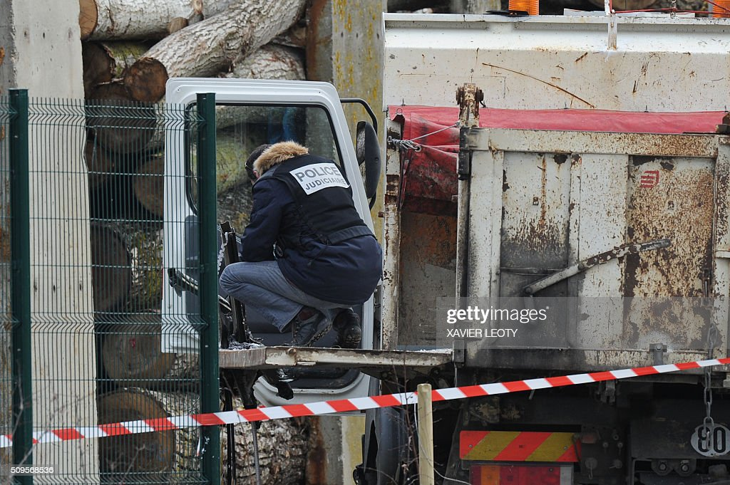A French forensic police officer works near the wreckage of a truck after it crashed into a school minibus in Rochefort on February 11, 2016, killing at least six children, police said, a day after another road accident involving a school bus left two youngsters dead. The head-on smash with a lorry carrying rubble came around 7:15 am (0615 GMT) in Rochefort in the western Charente-Maritime region. The school bus was carrying about 17 people, and three children suffered minor injuries in the accident, a police source said. / AFP / XAVIER LEOTY