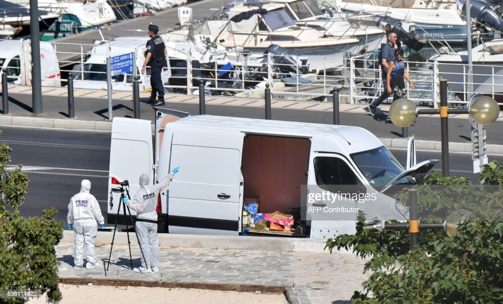 French forensic police officers gesture to pedestrians as they take images while searching a vehicle following a car crash in the southern Mediterranean city of Marseille on August 21, 2017. At least one person has died in Marseille after a car crashed into people waiting at two different bus stops in the southern French port city, police sources told AFP, adding that the suspected driver had been arrested afterwards. The police sources, who asked not to be identified, did not say whether the incident was being treated as a terror attack or an accident. /