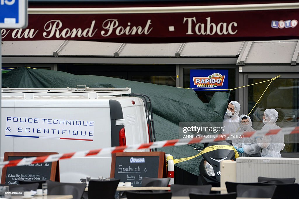 French forensic police officers look for evidence on November 26, 2012 in Marseille, southeastern France, in front of a cigar store where a 47-year old man was shot dead by two unidentified people who stole his briefcase.