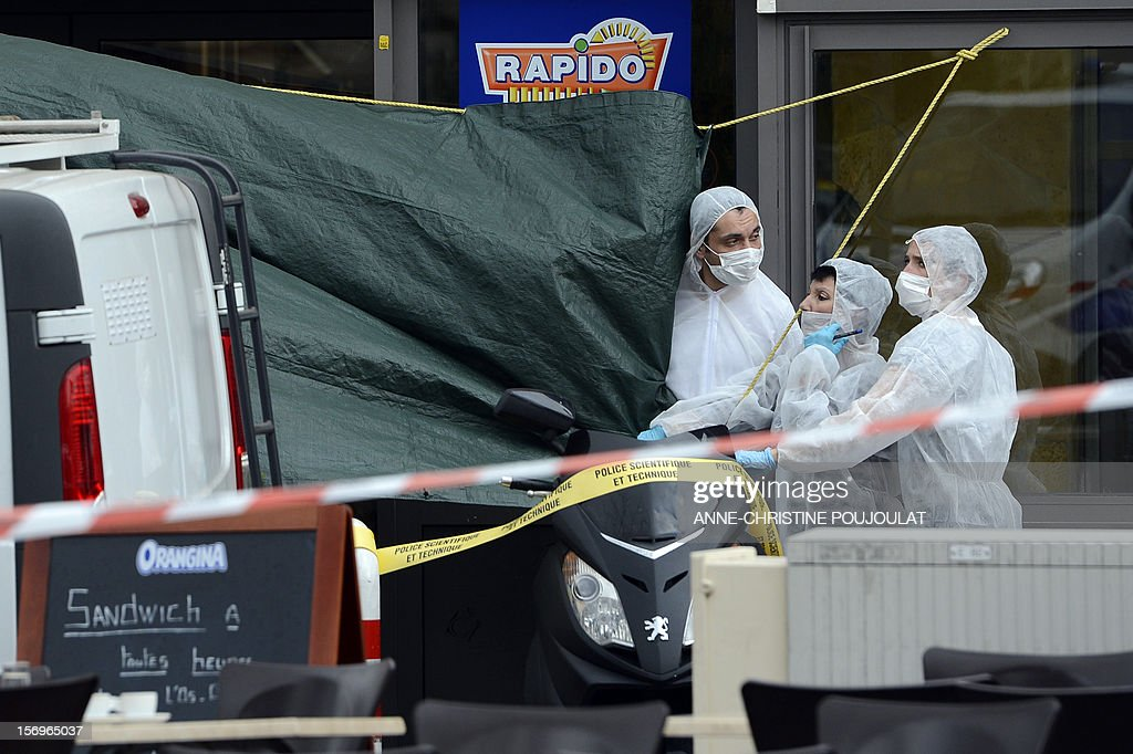 French forensic police officers look for evidence on November 26, 2012 in Marseille, southeastern France, in front of a cigar store where a 47-year old man was shot dead by two unidentified people who stole his briefcase. AFP PHOTO / ANNE-CHRISTINE POUJOULAT
