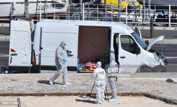 French forensic police officers take images as they search a vehicle following a car crash in the southern Mediterranean city of Marseille on August...