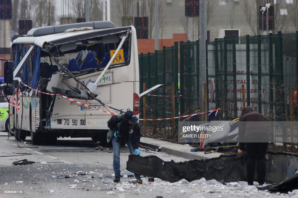 French forensic police work near the wreckage of a school minibus after it crashed into a truck in Rochefort on February 11, 2016, killing at least six children, police said, a day after another road accident involving a school bus left two youngsters dead. The head-on smash with a lorry carrying rubble came around 7:15 am (0615 GMT) in Rochefort in the western Charente-Maritime region. / AFP / XAVIER LEOTY