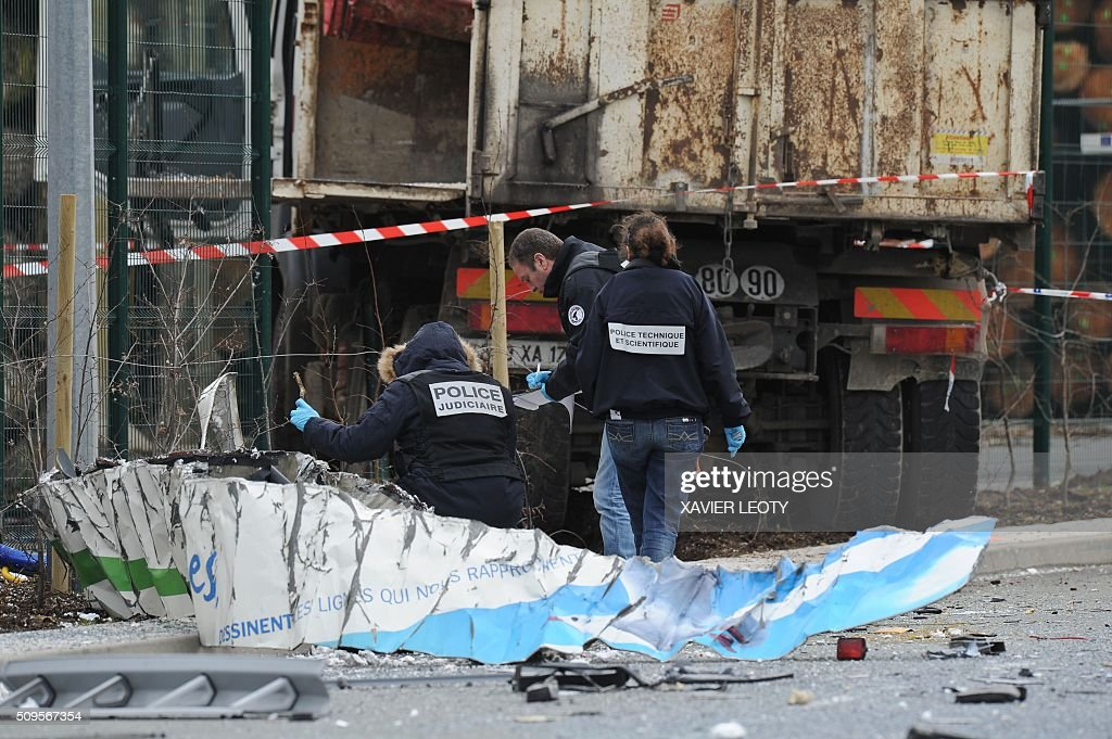 French forensic police work near the wreckage of a school minibus after it crashed into a truck in Rochefort on February 11, 2016, killing at least six children, police said, a day after another road accident involving a school bus left two youngsters dead. The head-on smash with a lorry carrying rubble came around 7:15 am (0615 GMT) in Rochefort in the western Charente-Maritime region. The school bus was carrying about 17 people, and three children suffered minor injuries in the accident, a police source said. / AFP / XAVIER LEOTY