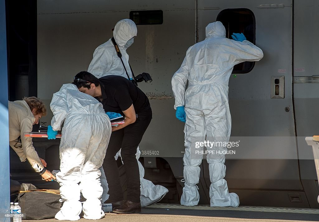 French forensics police officers wearing protective suits inspect the crime scene in a Thalys train of French national railway operator SNCF at the...
