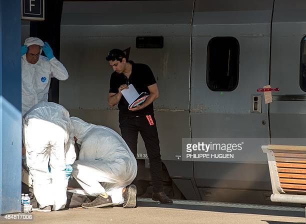 French forensics police officers wearing protective suits work at the crime scene near a sealed off Thalys train of French national railway operator...