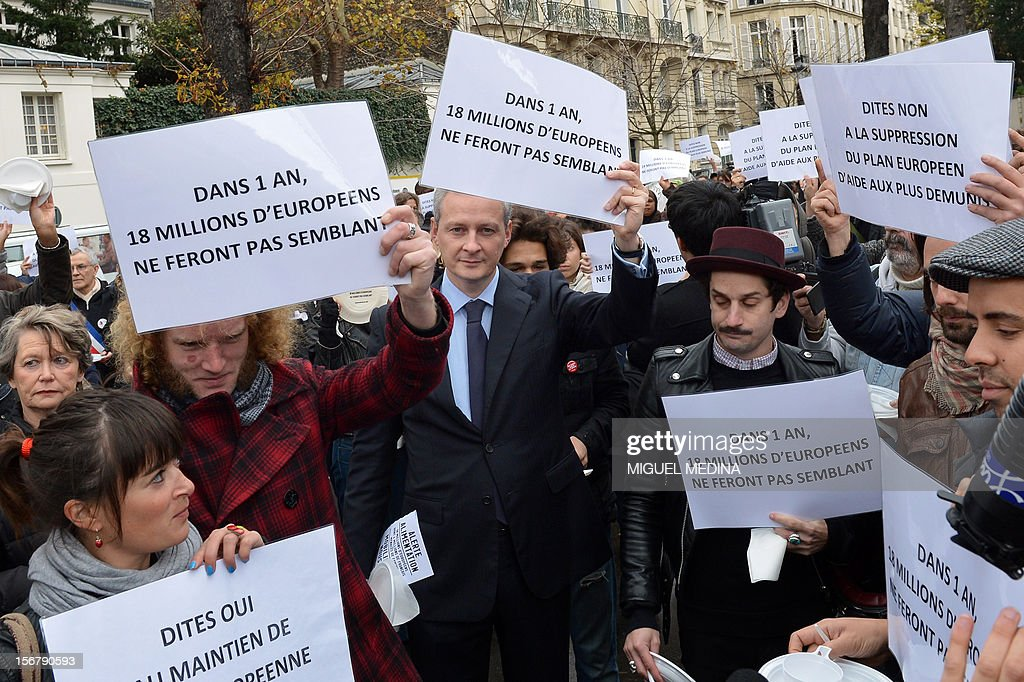 French former Agriculture minister Bruno Le Maire takes part in a 'Airfood' event, a giant air pic-nic without any food, organized by French association 'Secours Populaire' to ask for the renewal of a European food aid program on November 21, 2012 in front of the National Assembly in Paris. European heads of state will meet on November 22 and 23 and will take decisions on the European food aid. Papers read 'in 1 year, 18 millions european people will not pretend anymore'.