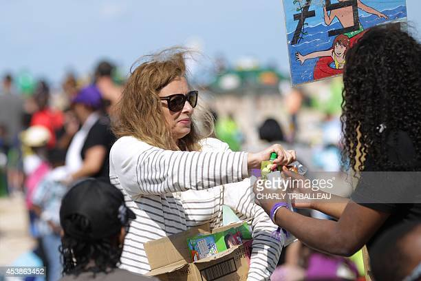 French former First lady Valerie Trierweiler gives a snack to children on a beach in Ouistreham northwestern France on August 20 2014 during the...