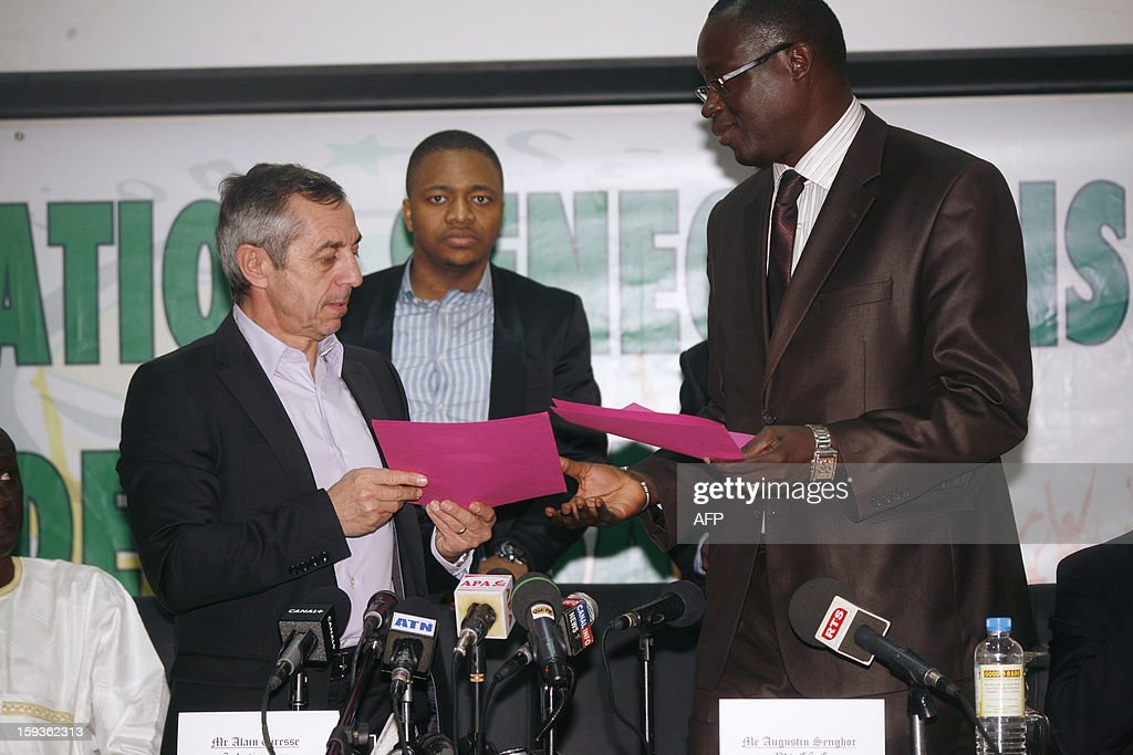 French former football international player Alain Giresse (L) gives a contract to Senegalese football federation president Augustin Senghor (R), after signing to be the new coach of the Senegal national football team, on January 11, 2013 in Dakar.