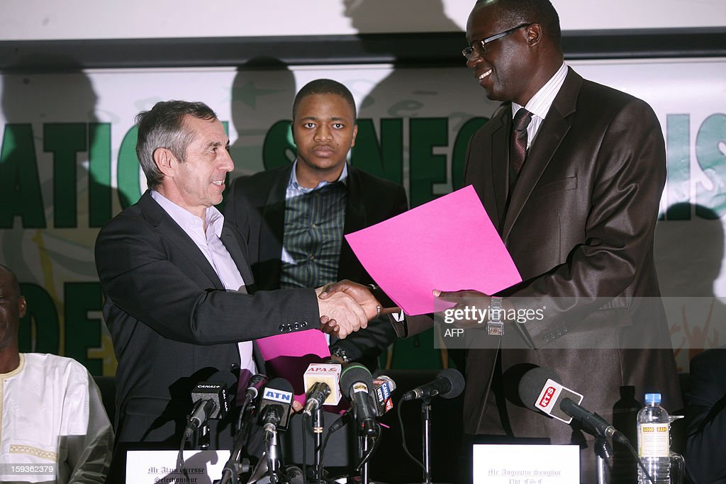 French former football international player Alain Giresse (L) shakes hands with Senegalese football federation president Augustin Senghor (R), after signing to be the new coach of the Senegal national football team, on January 11, 2013 in Dakar.