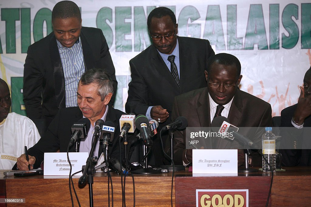 French former football international player Alain Giresse (L) signs a contract with Senegalese football federation president Augustin Senghor (R), to be the new coach of the Senegal national football team, on January 11, 2013 in Dakar. AFP PHOTO MAMADOU TOURE BEHAN