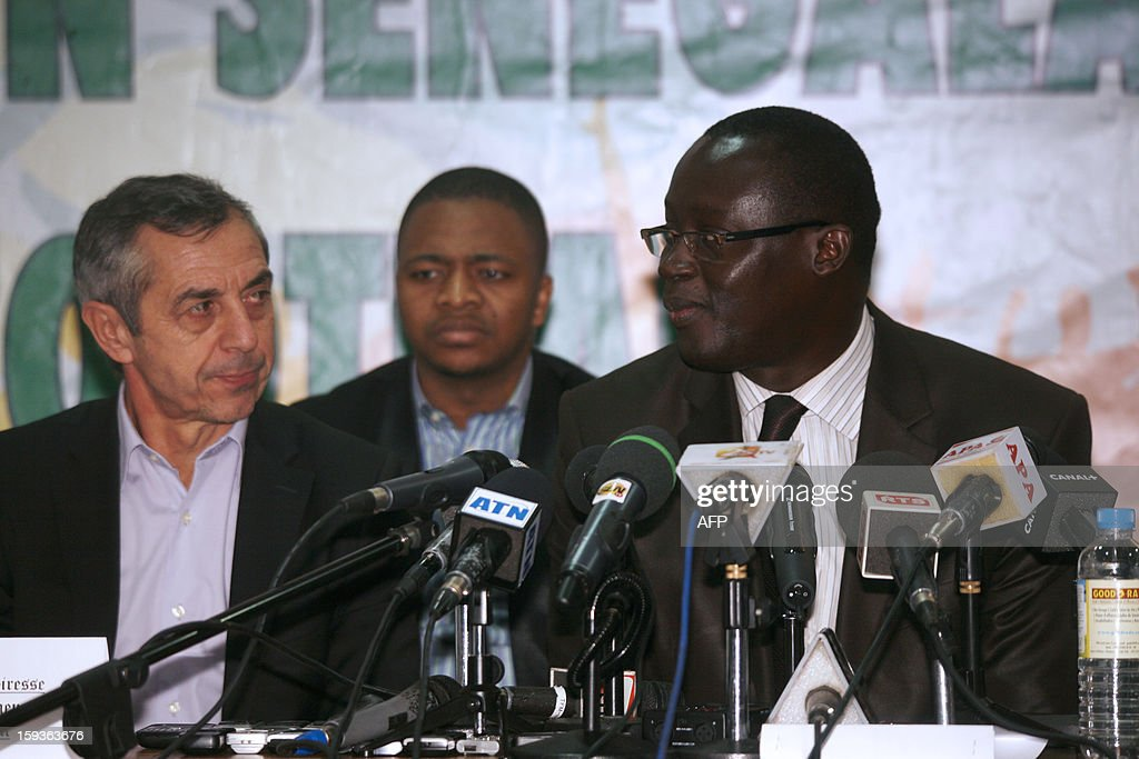 French former football international player Alain Giresse (L) sits alongside Senegalese football federation president Augustin Senghor (R), after signing to be the new coach of the Senegal national football team, on January 11, 2013 in Dakar.