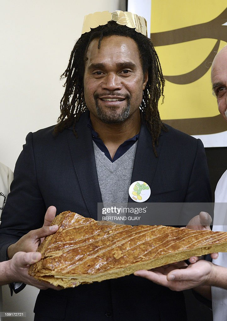 French former football player and good will ambassador of the 'Pieces Jaunes' (Small Coins) charity campaign's 24th edition, Christian Karembeu poses with a piece of a giant traditional Epiphany cake (galette des rois) on January 9, 2013 at the Andre Mignot Hospital in Le Chesnay, west of Paris, during the launch of the 'Pieces Jaunes' charity campaign's 24th edition.