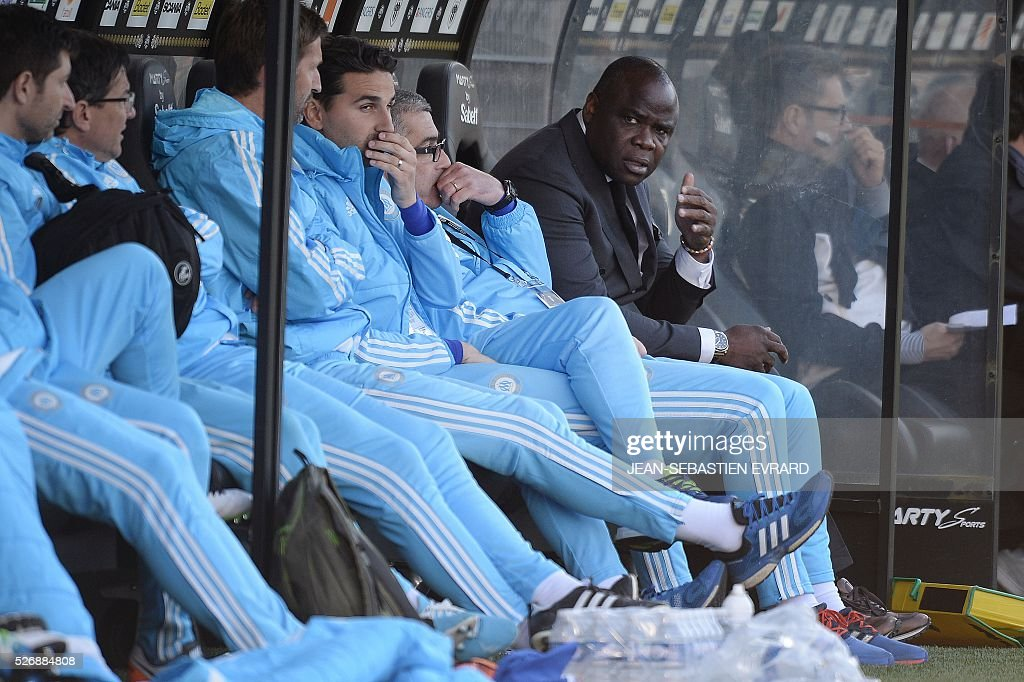 French former football player Basile Boli (R) attends during the French L1 football match between Angers and Marseille on May 1, 2016 at the Jean Bouin stadium in Angers, western France.