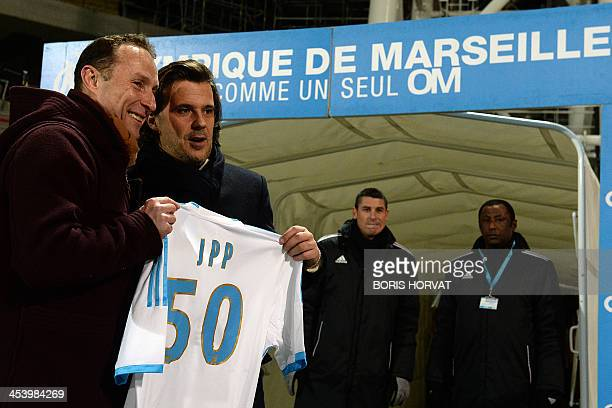 French former football player JeanPierre Papin poses with a Marseille team jersey bearing his initials and the number 50 after receiving it from...