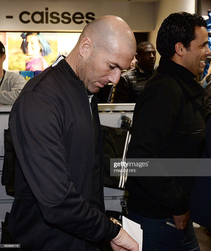 French former international player, Zinedine Zidane leaves a store of his sponsor on the Champs-Elysees avenue in Paris, on February 28, 2013. Beckham and French former international player Zinedine Zidane have autographed balls and jerseys for thirty fans selected via Twitter.