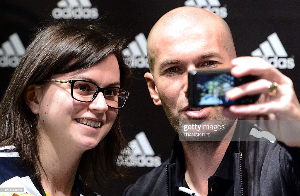 French former international player Zinedine Zidane poses with a fan in front of a store of his sponsor on the Champs-Elysees avenue in Paris, on February 28, 2013. Paris Saint-Germain's (PSG) English midfielder David Beckham and Zidane have autographed balls and jerseys for thirty fans selected via Twitter.