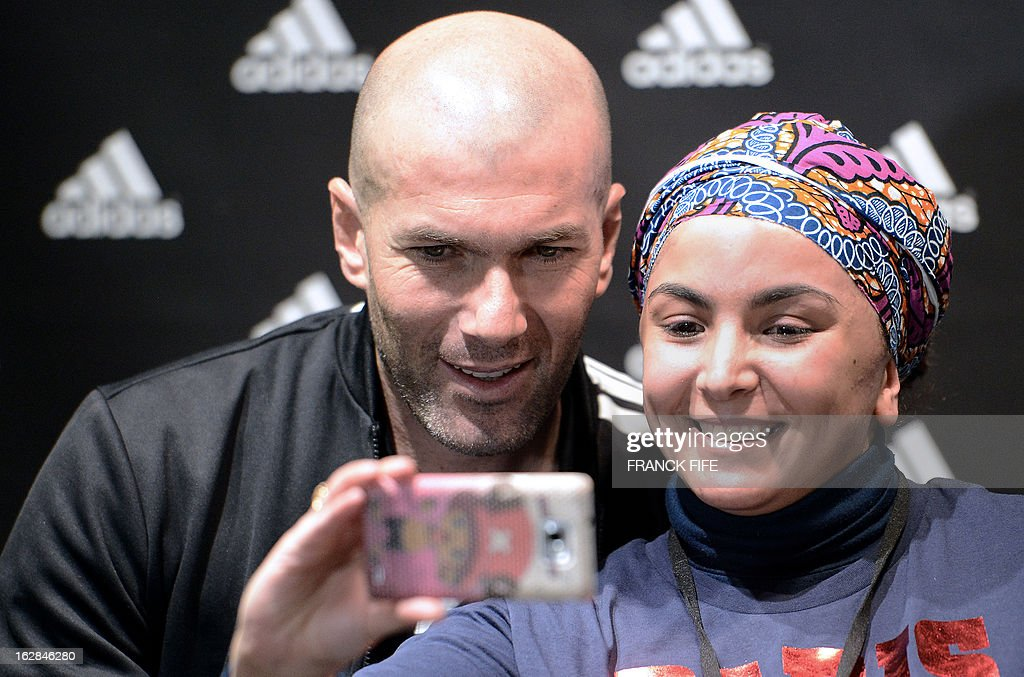 French former international player Zinedine Zidane poses with a fan in front of a store of his sponsor on the Champs-Elysees avenue in Paris, on February 28, 2013. Paris Saint-Germain's (PSG) English midfielder David Beckham and Zidane have autographed balls and jerseys for thirty fans selected via Twitter. AFP PHOTO/ FRANCK FIFE