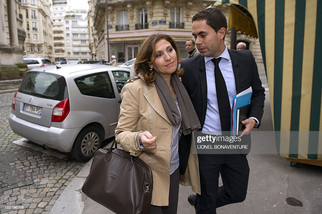 French former junior Minister Nora Berra arrives with communication adviser Lionel Moisy de Cala to attend a breakfast gathering the members of the the association 'The friends of Nicolas Sarkozy', on October 9, 2012 in Paris.