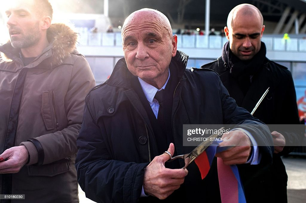 French former Lyon's player Fleury Di Nallo cuts the ribbon during the 'The avenue of lights' inauguration at the Parc Olympique Lyonnais stadium in Decines-Charpieu, central-eastern France on February 14, 2016 before the French L1 football match between Olympique Lyonnais (OL) and Stade Malherbe Caen (SMC). / AFP / CHRISTOF STACHE