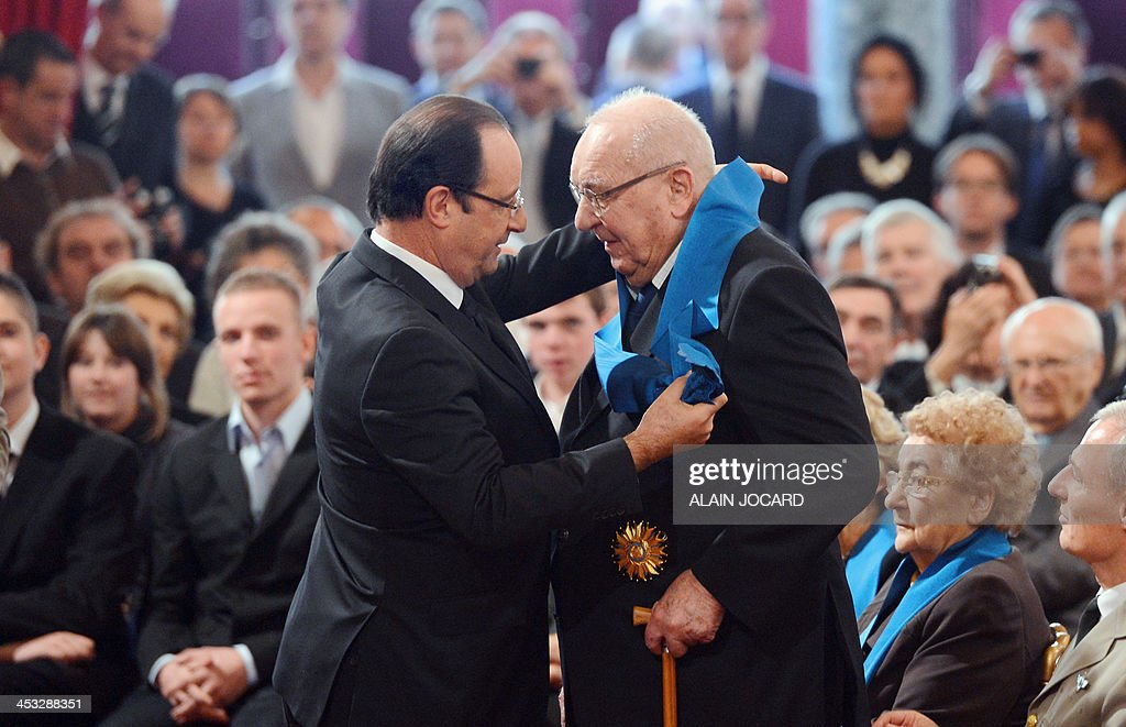 French former magistrate and Cannes film festival honorary president Pierre Viot (R) is awarded as 'Grand'Croix' in the 'Ordre national du Merite' (national Merit Order) by French President Francois Hollande during a ceremony at the Elysee presidential palace on December 3, 2013 in Paris.