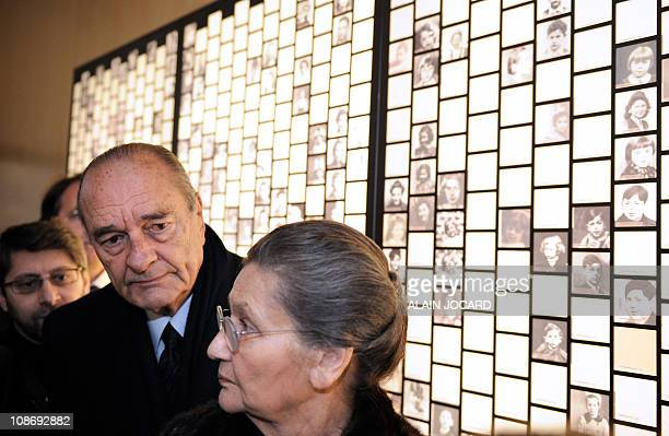 French former President Jacques Chirac and French former Minister Simone Veil former Auschwitz death camp's survivor look at photographs of victims...