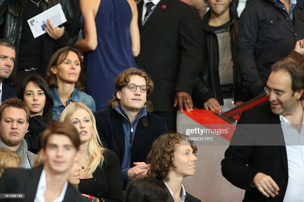 French former President's son Jean Sarkozy (C) and founder of the group Iliad and shareholder of French newspaper Le Monde, Xavier Niel (R) attend the French L1 football match Paris Saint-Germain (PSG) vs Monaco (ASM), on September 22, 2013 at the Parc des Princes stadium in Paris.