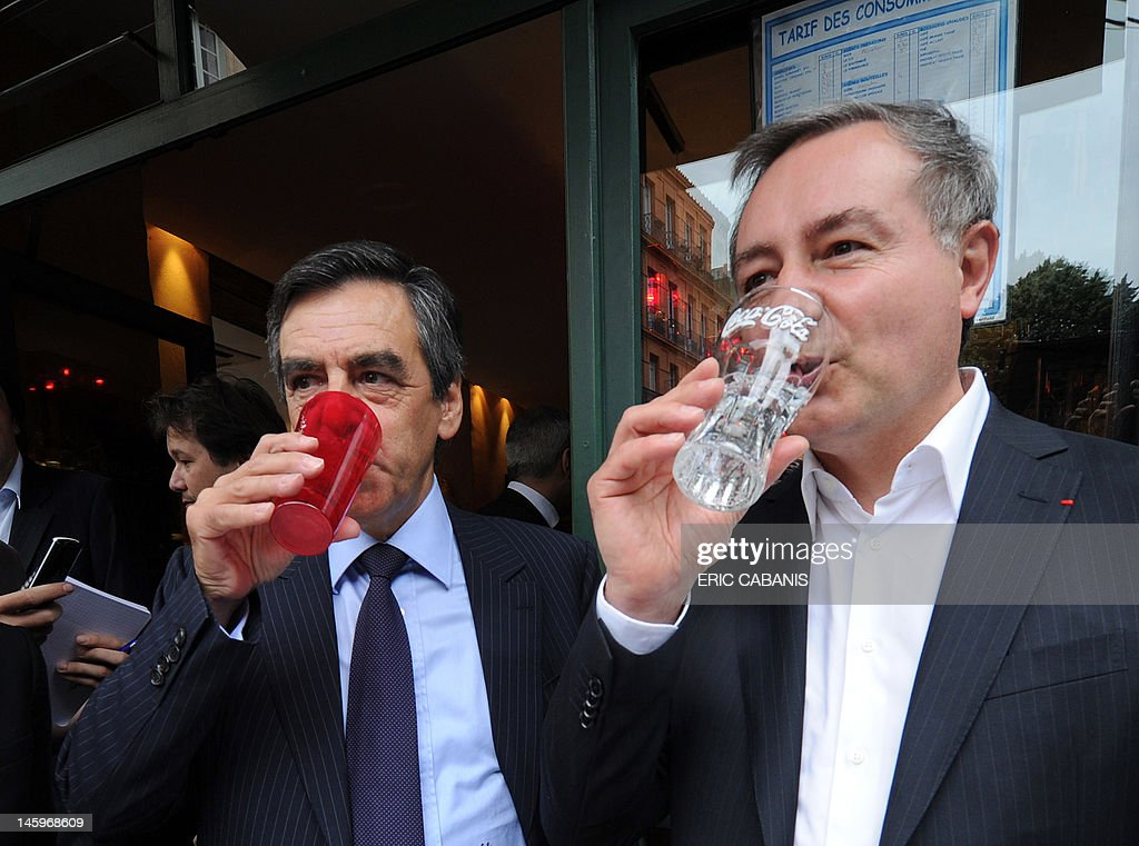 French former Prime Minister Francois Fillon (L) and Jean-Luc Moudenc (R), UMP right-wing ruling party candidate for the June 2012 French parliamentary election in the 3rd constituency of Haute-Garonne department, drink in a bar during a campaign visit on June 8, 2012 in Toulouse, southwestern France.
