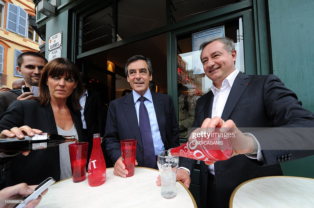 French former Prime Minister Francois Fillon (C), Jean-Luc Moudenc (R), UMP right-wing ruling party candidate for the June 2012 French parliamentary election in the 3rd constituency of Haute-Garonne department and his substitute Laurence Arribage (L), drink in a bar during a campaign visit on June 8, 2012 in Toulouse, southwestern France.