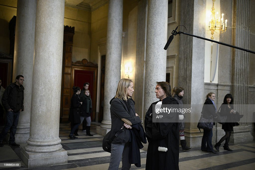 French former tennis player Isabelle Demongeot (C) discusses with civil party lawyer Jean-Claude Guidicelli (R) outside a courtroom on November 23, 2012 at Lyon's courthouse, while waiting for the verdict in the trial of former tennis coach Regis de Camaret, who appears for rapes on two under-age women, twenty years ago.