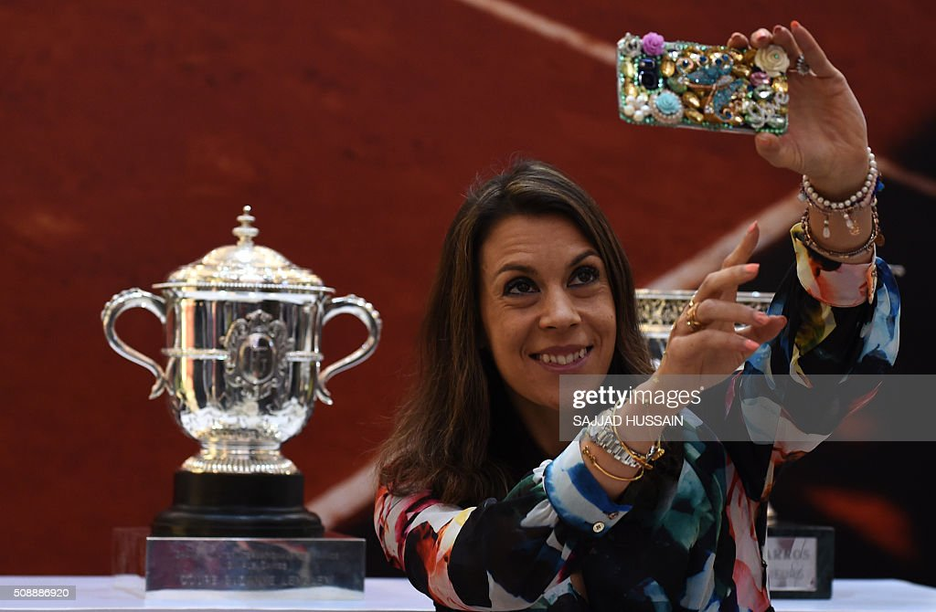 French former tennis player Marion Borteli takes a selfie with the French Open trophy at a shopping mall in New Delhi on February 7, 2016. This year's championship will be played from May 22 to June 5. AFP PHOTO / SAJJAD HUSSAIN / AFP / SAJJAD HUSSAIN