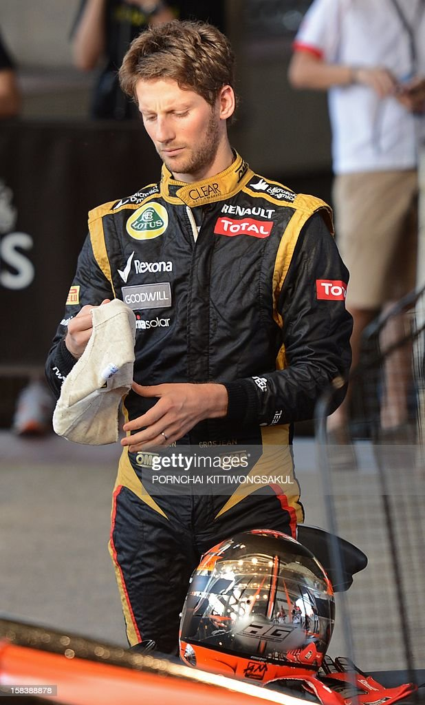 French Formula One racing driver, Romain Grosjean holds a head guard during a practice session ahead of the annual Race of Champions (ROC) at Rajamangala Stadium in Bangkok on December 15, 2012. The Race of Champions (ROC) will take place in Thailand between December 14 and 16 and brings together heavyweights from all motor racing disciplines in the same type of car.