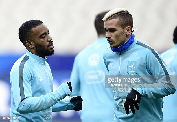 French forward Alexandre Lacazette speaks with French forward Antoine Griezmann during a training session on March 25 on the eve of the team's...