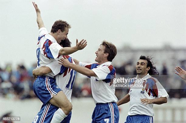 French forward JeanPierre Papin jubilates with defensive midfielder Didier Deschamps and left defender Eric Di Meco on September 5 1990 in Reykjavík...