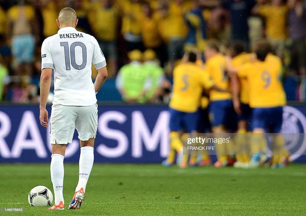 French forward Karim Benzema reacts as Swedish players celebrate their goal during the Euro 2012 football championships match Sweden vs France on June 19, 2012 at the Olympic Stadium in Kiev.