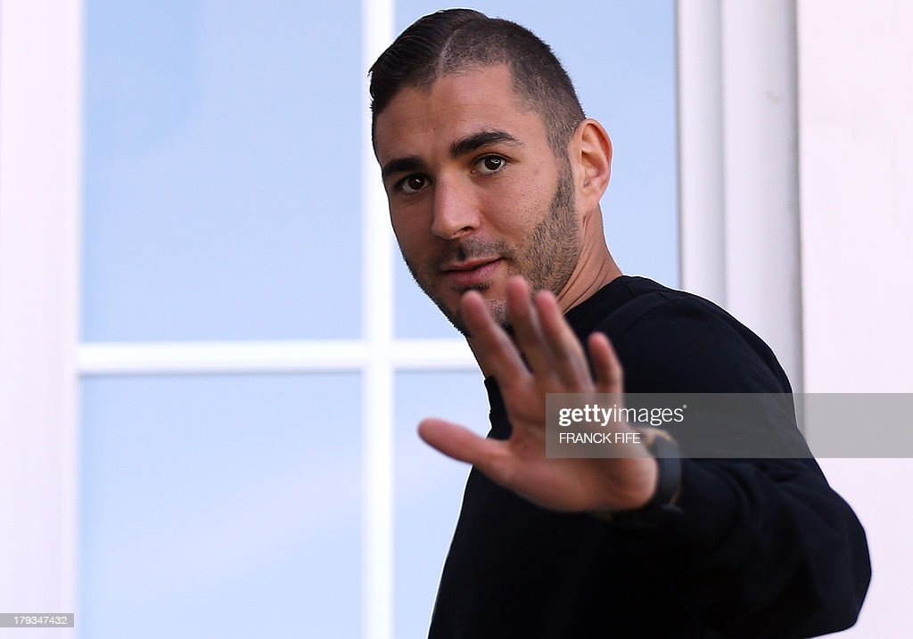 French forward Karim Benzema waves as he arrives at the French national football team training base in Clairefontaine-en-Yvelines, near Paris, on September 2, 2013 on the first day of their training ahead of the WC2014 qualifying football match against Georgia and Belarus.