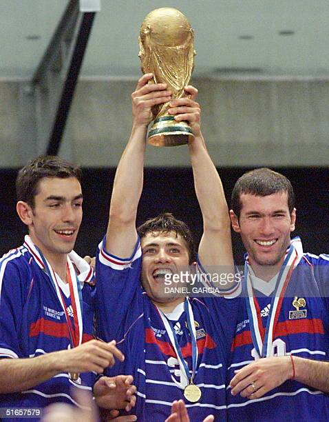 French forward Robert Pires is flanked by defender Bixente Lizarazu and midfielder Zinedine Zidane as he holds the FIFA trophy 12 July at the Stade...