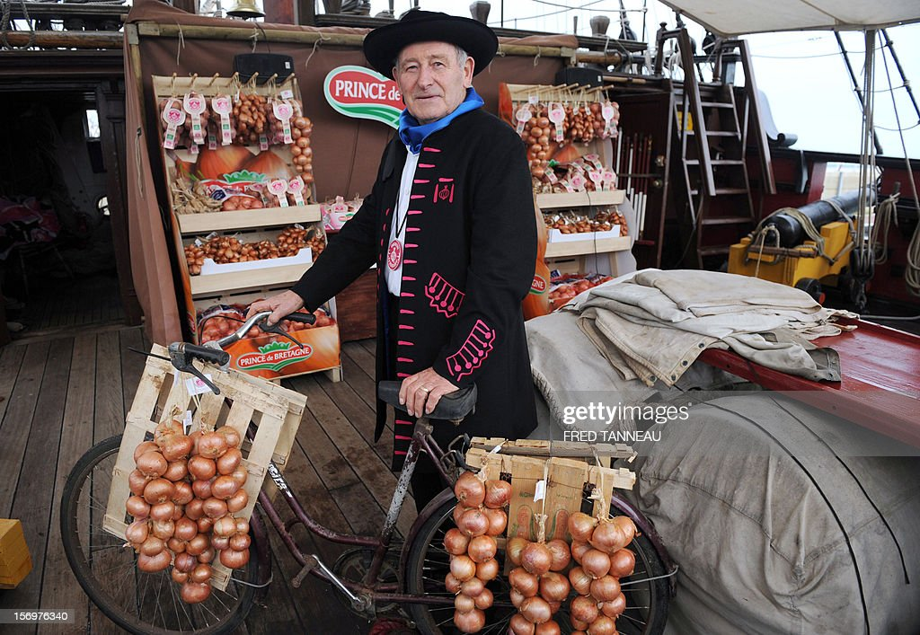 French Francois Seite, President of the 'Onion Johnnies' association, poses with pink onions destined for Great Britain aboard the Etoile du Roy (Star of the King), a replica of an 18th-century sailing ship, on November 24, 2012 in Roscoff, western France. 'Onion Johnnies', the travelling salesmen whose berets and bicycles inspired Britain and much of the world's classic image of the archetypal Frenchman, are setting sail for England once more. The boat, weighed down by the hefty cargo, will assure the delivery of the onions to London on December 6, after stopovers on the Channel island of Jersey and at Portsmouth, on England's southern coast. The first French onion salesman to try his luck in England set sail from Roscoff in 1828.