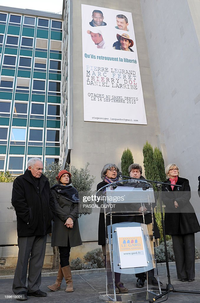 French Francoise Larribe (C), herself former hostage, and wife of Daniel Larribe, one of the four French hostages captured in Niger and detained since 28 months in Mali by AQIM, delivers a speech during a ceremony y in support to the hostages after a poster of the four men was hung on the facade of the General Council building (background), on January 17, 2013 in Nimes, southern France. The four French hostages were in a group of seven captured in Niger's uranium-mining town of Arlit. The 'Serval' French military operation backing Mali's army in battling Islamist insurgents currently has some 1,400 soldiers deployed, some of whom are engaged in ground operations. Second left, Marion Larribe, daughter of Daniel Larribe, second right, Damien Alary, president of the Gard General Council.
