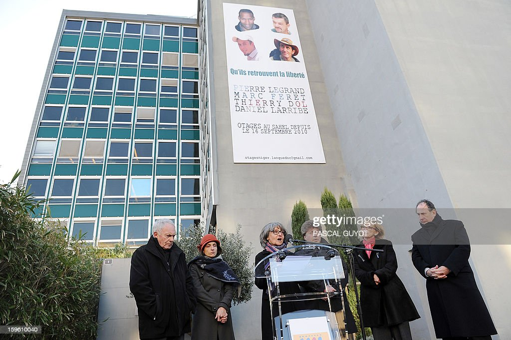 French Francoise Larribe (C), herself former hostage,and wife of Daniel Larribe, one of the four French hostages captured in Niger and detained since 28 months in Mali by AQIM, delivers a speech during a ceremony y in support to the hostages after a poster of the four men was hung on the facade of the General Council building (background), on January 17, 2013 in Nimes, southern France. The four French hostages were in a group of seven captured in Niger's uranium-mining town of Arlit. The 'Serval' French military operation backing Mali's army in battling Islamist insurgents currently has some 1,400 soldiers deployed, some of whom are engaged in ground operations. Second left, Marion Larribe, daughter of Daniel Larribe, third right, Damien Alary, president of the Gard General Council.