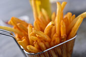 closeup of some appetizing french fries served in a metal basket on a gray rustic wooden table