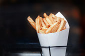 French fries in paper bundle. Dark background. Place for text and copyspace